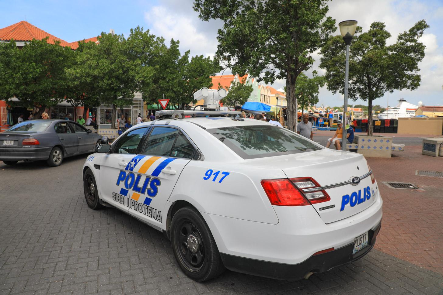 Een politieauto op Curacao die aan het rondrijden is.